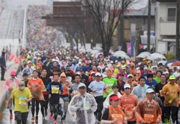 雨の中、熊本西大橋一帯を埋めるフルマラソンのランナーたち=熊本市南区(小野宏明)