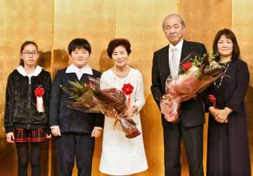 夫の喬さん(右から2人目)と共に孫らから花束を受け、笑みを浮かべる三宅さん(中央)