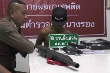Jakkrit, right, at  Nang Rong police station in Buri Ram province after his arrest. He fired more than 40 shots with a handgun in a community late on Sunday afternoon. (Photo by Surachai Piragsa)