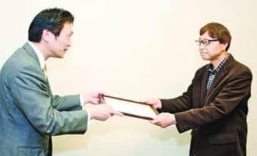 贈呈書を受け取る本田事務局長右