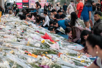 People lay flowers and write condolence messages in front of Terminal 21 in Nakhon Ratchasima, in memory of those who lost their lives in the shooting. Photo courtesy of Terminal21Korat.