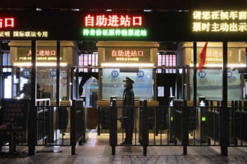 A train attendant waits to check passengers at a deserted Beijing railway station on Friday evening, Feb 14, 2020. (NYT photo)