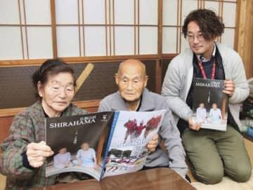 コンクールで入賞した広報を読む久村一夫さん・久子さん夫妻と担当職員の大平幸宏さん(右)=和歌山県白浜町上露で