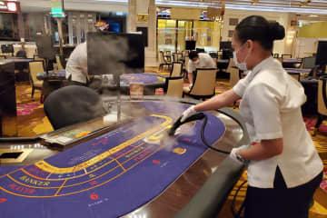 マカオのカジノ施設における高温スチームクリーナーを使ったゲーミングテーブルの清掃の様子(写真:DICJ)