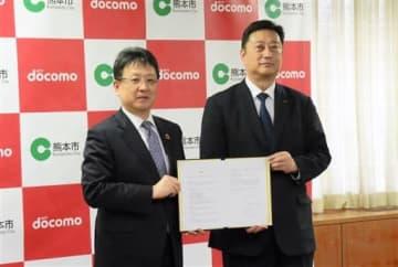 高齢者見守りサービスの社会実験に向け連携協定を結んだ熊本市の大西一史市長(左)とNTTドコモ九州支社の山崎拓支社長=熊本市役所