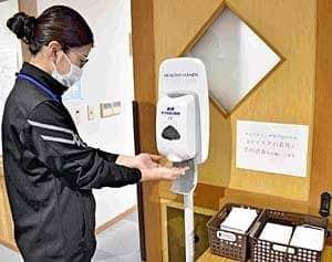 手をアルコール消毒する養護老人ホーム「会津長寿園」の職員。高齢者を預かる施設は感染症対策の強化を図る