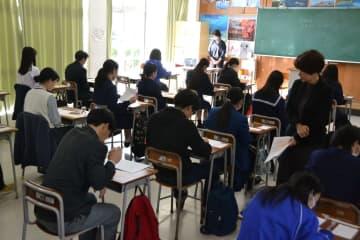 解答用紙に名前などを記入する受験生=1日、西原町翁長の沖縄キリスト教学院大学・短期大学