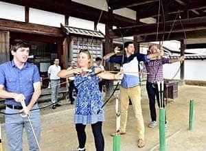 欧米の記者を対象にした会津若松市主催のツアーで弓道を楽しむ参加者。武士道文化への関心は高い=2018年、会津若松市・會津藩校日新館