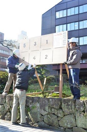 熊本市議会棟前に知事選のポスター掲示場を設置する作業員=19日、熊本市中央区