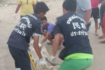 Rescue workers carry the body of an unidentified man washed ashore in Hua Sai district, Nakhon Si Thammarat on Wednesday. (Photo supplied by Nujaree Raekrun)