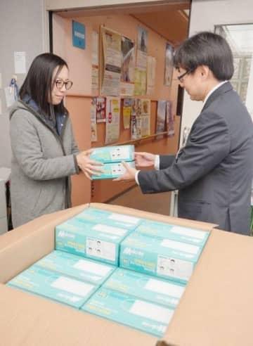 窓口を訪れた医療・福祉施設の職員にマスクを渡す市職員(右)