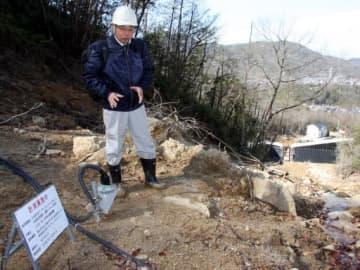 大原ハイツの裏山の土石流跡に設置した傾斜計について説明する土田センター長。奥右下は県が整備した砂防ダム