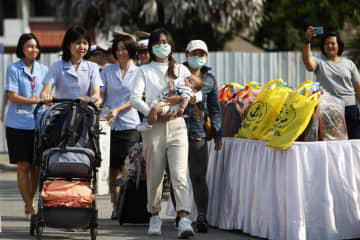 A woman with her baby is assisted by nurses as she leaves the Covid-19 quarantine facility at the naval base in Chon Buri on Wednesday.