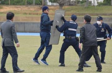 聖火リレー開催中を想定し、不審者を取り押さえる警察官=18日、浦添市
