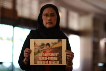 Thailand's former human rights commissioner Angkhana Neelapaijit holds a placard showing the #FreeMuay campaign to raise awareness about the imprisonment of Lao activist Houayheuang 'Muay' Xayabouly.NETIWIT CHOTIPHATPHAISAL
