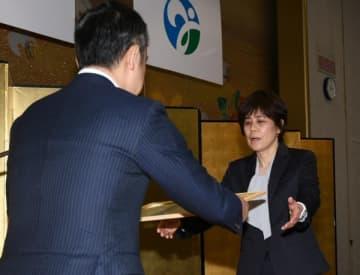 【県スポーツ特別功労賞を受賞した向田真優選手の代理として表彰される母・啓子さん(右)=津市内で】