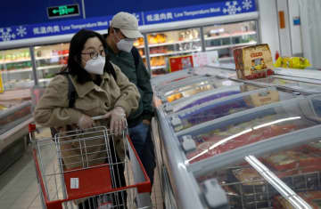 People wearing face masks look for products at a supermarket, as the country is hit by an outbreak of the new coronavirus, in Beijing (photo credit: REUTERS)