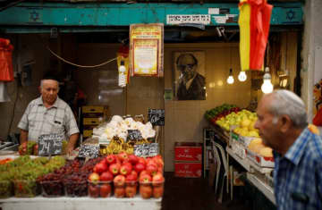 A man walks past a fruit and vegetable stall in a market in Jerusalem (photo credit: REUTERS/AMIR COHEN)