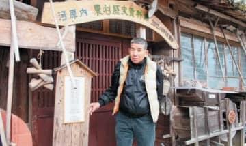 昔の農具や生活用品を展示した農村歴史資料館を案内する河原内自然環境保全くらぶ世話人の坂本裕明さん=大分市河原内