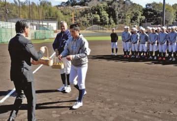 真砂充敏市長(左)から特産品を受け取る近畿大学硬式野球部の谷本甲仁主将=19日、田辺スポーツパークで