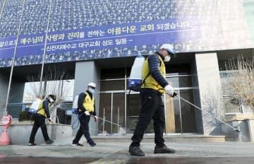 新型コロナウイルスの感染が相次いで発生した韓国・大邱の教会周辺を消毒する保健所の関係者=2月20日(聯合=共同)