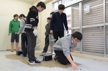 高校生の活動拠点「ひたちマチラボidea」のオープンに向け床にペンキを塗り、改装作業を進める高校生と市民有志たち=日立市鹿島町