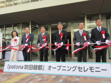 「patona 吹田健都」の竣工を祝ってテープカットする井上社長(左から3番目)ら関係者
