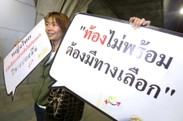 A social activist holds placards calling for legal abortion during a campaign in 2016.Bangkok Post photo