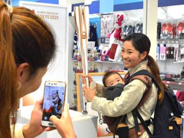 東京五輪の聖火リレーのトーチを持って記念撮影する来店客=岐阜市正木中、マーサ21