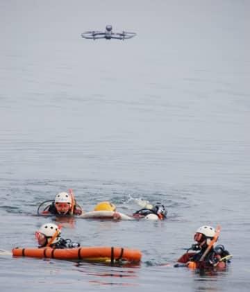 【頭上のドローンの誘導で要救助者を捜索する訓練参加者ら=鈴鹿市白子1丁目の白子港内で】