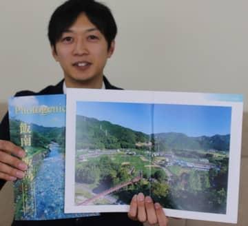 【飯南・飯高地域の風景写真集「Photogenic166」を示す中西さん=松阪市役所で】