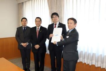 前田副社長(右)に要望書を手渡す田上市長=福岡市、JR九州本社