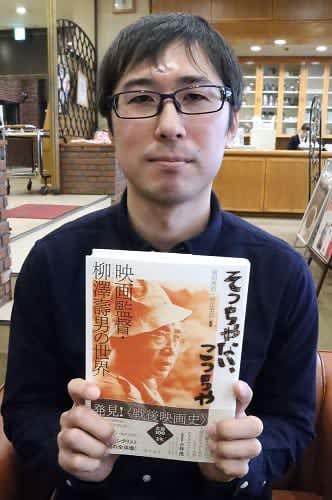 柳澤監督の業績をまとめた本「そっちやない、こっちや」を手にする西さん=長崎新聞社