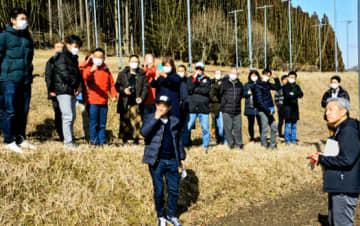 鈴木さん(手前右)のホップ畑を見学する参加者