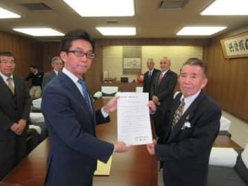 【伊藤市長(手前左)に出馬要請書を提出した藤原会長ら=桑名市役所で】