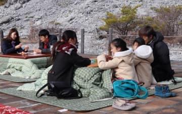 エコタツで暖を取る観光客=2019年2月10日、雲仙市、旧八万地獄