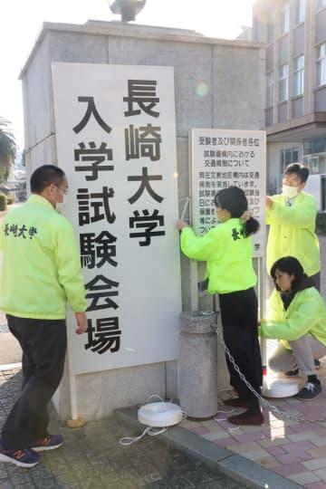 正門に立て看板を設置する職員=長崎市文教町、長崎大