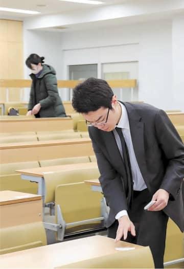 試験会場の机に受験番号が書かれた紙を貼る職員=東北大川内北キャンパス
