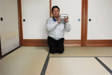 衝撃緩和型畳床「セーブ畳床」を敷いた和室で、模型を手にする岡部商事の岡部龍太郎社長=八代市