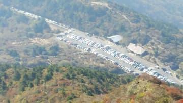 大勢の行楽客らで満車状態の駐車場。駐車待ちの車が列をつくる(写真左上)=2019年11月3日、雲仙市の仁田峠(渋滞対策協議会提供)