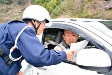 ドライバーに緊張感を持った運転を呼び掛ける八幡浜署員(左)
