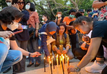 Participants light candles during a pro-democracy rally at the Tha Prachan campus of Thammasat University on Saturday evening. (Aekarach Sattaburuth)