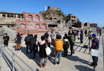 上陸しガイドの説明を受ける観光客=長崎市、端島