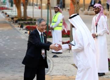 夕食会の会場に到着し、歓迎を受ける黒田東彦日銀総裁=22日、サウジアラビア・リヤド(ロイター=共同)