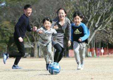 暖かい日差しの中、サッカーを楽しむ家族連れ=22日午後、大分市の七瀬川自然公園