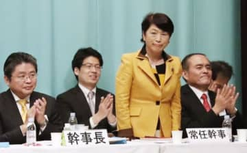 社民党大会で福島瑞穂新党首が選出され、拍手をする吉田忠智参院議員(右端)と吉川元・幹事長(左端)=22日午後、東京都千代田区
