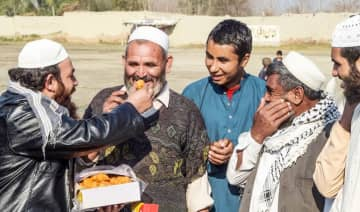 An Afghan refugee distributes sweets on the outskirts of Peshawar to celebrate the step toward peace agreed between Taliban, US and Afghan forces.