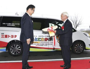 【鍵のレプリカを前葉市長(左)に手渡す三重トヨタ自動車の竹林会長=津市内で】