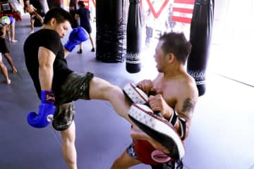 Businessman Chatri Sityodtong (left) attends a Muay Thai training session.