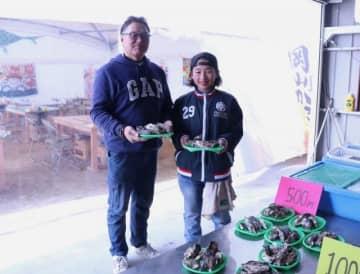 近所の子供の手も借りてカキ小屋を営む竹田さん(左)